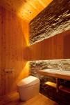 石の壁と照明によるトイレの演出。
